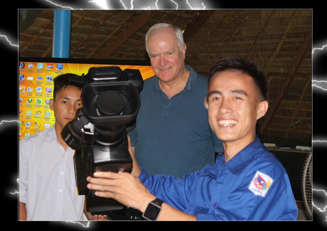 """Rex Bates presents the Video Camera to Nouchai and Yaa Tua, the 2 camera men for the film """"An Unlikely Friendship"""""""